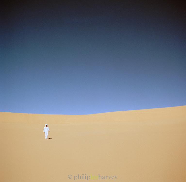Man walking across sand dunes of the Sahara desert in robes, Libya