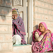 Elderly couple sitting in front of home in village of Chandelao, Rajasthan