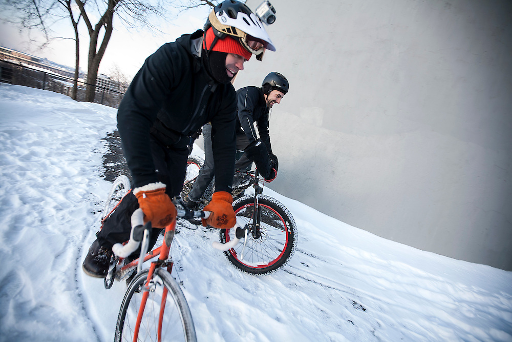 Gene Oberpriller, left, co-owner of One on One Bicycle Studio, and Rob Williams ride around the water tower as they man the check-in point at Prospect Park during Stupor Bowl 17 in Minneapolis February 1, 2014.