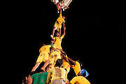 A team of men is collaborating to create a human pyramid, in order to win a cash prize during the festival of Janamashtami, the birthday of Hindu God Krishna, in Bhopal, Madhya Pradesh, India, site of the infamous 1984 gas tragedy. The poisonous cloud that enveloped Bhopal left everlasting consequences that today continue to consume people's lives.