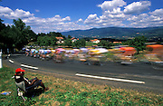 The peloton sweeps downhill towards Ambert during Stage 19 of the 2005 Tour de France.