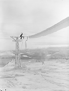 """ackroyd-01177-47. Timberline. December 16, 1948. 41/48Repairing the Magic Mile chair lift. """"Prior to weather clearing on Dec 16, 1948 there had been an utterly miserable blizzard for days. Weather so bad that some of the Magic Mile cable was completely blown off the towers, some chairs being blown all the way 'round in 360 degrees. Measured weight of snow and ice on cables and chairs was estimated 25# to the foot. Repeated sledgehammer blows required to clear the buildup. Great ingenuity (was required) to rotate the chairs in a reverse 360."""""""