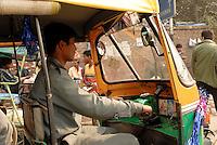 A auto  rickshaw drivers navigates the busy Delhi Streets, India