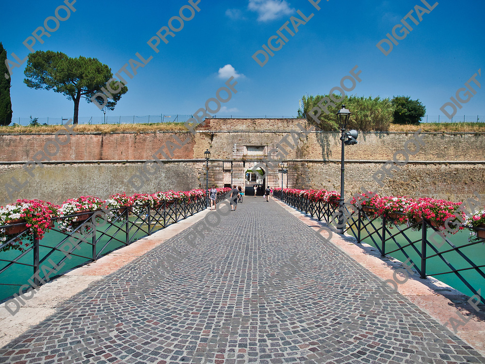 Entrance bridge to peschiera del garda village in Garda Lake Italy adorned with flowers during a summer afternoon. The bridge connects with the Porta Brescia