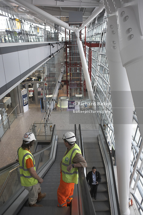 Construction workers on escalator in landside Arrivals area of  newly-opened London Heathrow Airport's Terminal 5 building.