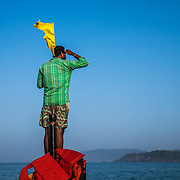 A boat operator on the lookout for dolphones during an early mornign dolphin viewling trip. A boat is like a taxi on Agonda beach, and many poeple use the boats for dolphone viewing trips, or short excursions to the nearby smaller and more secluded beaches like Honeymoon beach, or Butterfly beach.