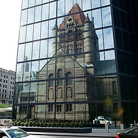 Trinity Church, built in 1877, reflected in the glass facade of the John Hancock Tower, in Copley Square in Boston