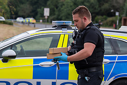© Licensed to London News Pictures. 27/07/2021. Stoke Poges, UK. A police officer carries evidence on Bells Hill in Stoke Poges, Buckinghamshire, following an assault on Monday 26 July at approximately 21:30BST. A man in his twenties suffered a serious leg injury following the assault which is understood to have involved a machete. Two men, aged 19 and 21, and a 20-year-old woman have been arrested on suspicion of section 18 wounding with intent. Photo credit: Peter Manning/LNP