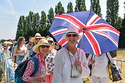 © Licensed to London News Pictures. 06/07/2018. LONDON, UK. Spectators queuing for day tickets in Wimbledon Park to the Wimbledon Tennis Championships shelter under an umbrella.  Temperatures forecast to approach 30C mean that the majority have taken precautions to protect themselves from the sun by wearing sunglasses and sunhats.  Photo credit: Stephen Chung/LNP