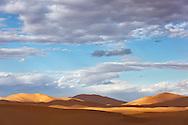 Erg Chebbi sand dunes with cloudy blue sky, Merzouga, Morocco.