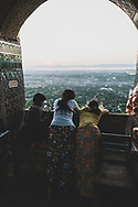 Mandalay, Myanmar - November 8, 2011: Locals atop Mandalay Hill at sunset.