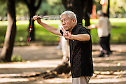 An elderly Chinese man practices martial arts sword exercise early morning at the Temple of Heaven Park during summer in Beijing, China