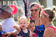 A young family wearing patriotic costume during the annual Sullivan's Island Independence Day parade July 4, 2017 in Sullivan's Island, South Carolina. The tiny affluent sea island hosts a bicycle and golf cart parade through the historic village.