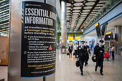 """© Licensed to London News Pictures. 09/04/2021. London, UK. Flight attendants walk past a government information sign at London Heathrow. Today, Transport Secretary Grant Shapps sets out details of the government's """"traffic Light"""" system for May 17th so that the public can travel abroad with passengers requiring to take a private covid-19 test each way, costing as much as £150.00 for one test. Photo credit: Alex Lentati/LNP"""