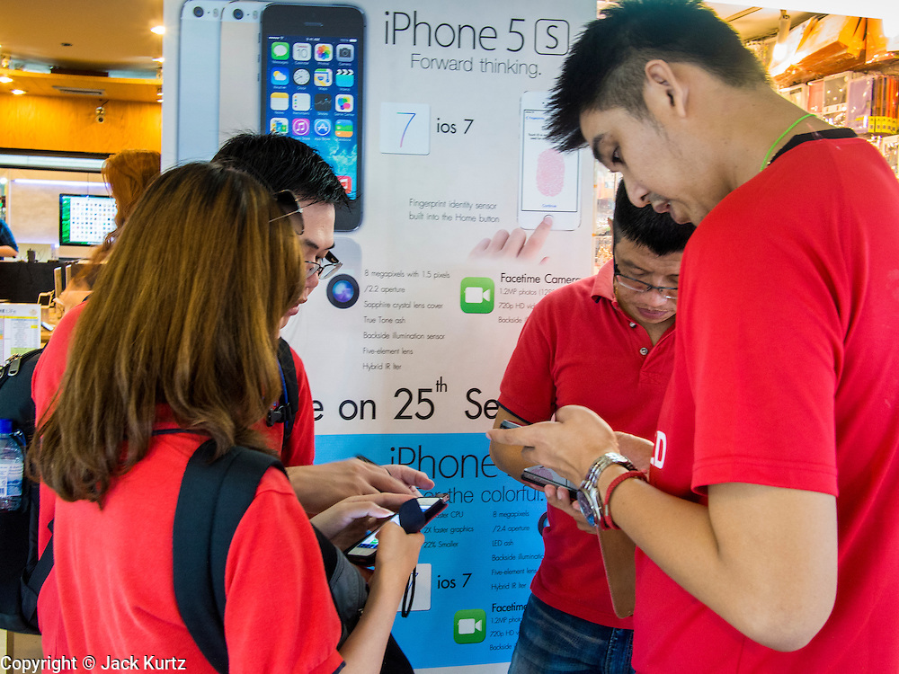 21 SEPTEMBER 2013 - BANGKOK, THAILAND: A group of shoppers set up their iPhone 5s phones after purchasing them in MBK in Bangkok. Customers around the world lined up Friday to pick up Apple's new flagship iPhone 5s and its lower cost, more colorful brother, the iPhone 5c. The phones went on sale in the US and select countries beyond the US on Friday. The iPhone 5s and iPhone 5c will not be officially released in Thailand until late 2013 but the phones are available through the unofficial grey market in MBK, a huge shopping complex in Bangkok with dozens of small electronics shops. Early purchasers in Thailand pay a premium for the new iPhones, the top of the line iPhone 5s with 64 gigabytes of memory is about 38,500Baht, more than $1,200 (US).      PHOTO BY JACK KURTZ