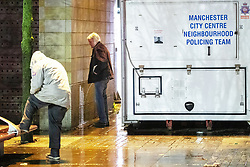 """© Licensed to London News Pictures . 21/12/2018 . Manchester , UK . A man urinates behind a police caravan in Piccadilly Gardens . Revellers out in Manchester City Centre overnight during """" Mad Friday """" , named for historically being one of the busiest nights of the year for the emergency services in the UK . Photo credit : Joel Goodman/LNP"""