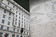 The tall architecture of office spaces above Green Park Underground station on Piccadilly left and the wall of the station opposite the road, that features the imprints of sea creatures and sea shells indented into the concrete, on 25th February 2020, in London, England.