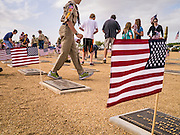 26 MAY 2012 - PHOENIX, AZ: People walk through the National Memorial Cemetery in Phoenix, AZ, Saturday. Hundreds of Boy and Girl Scouts along with the Young Marines, a Scout like organization, place American flags on veterans' graves in the National Memorial Cemetery in Phoenix every year on the Saturday before Memorial Day.       PHOTO BY JACK KURTZ