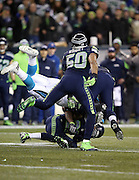 Seattle Seahawks outside linebacker K.J. Wright (50) closes in as Carolina Panthers fullback Mike Tolbert (35) gets upended as he gets gang tackled after making a first quarter pass reception during the NFL week 19 NFC Divisional Playoff football game against the Seattle Seahawks on Saturday, Jan. 10, 2015 in Seattle. The Seahawks won the game 31-17. ©Paul Anthony Spinelli