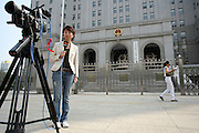 A journalist from Hong Kong reports from in front of the Beijing court house where the sentencing of Hong Kong reporter Ching Cheong took place August 31, 2006. Ching was sentenced to five years in prison on espionage charges, the latest step in a widening Chinese crackdown on the media and on dissent.