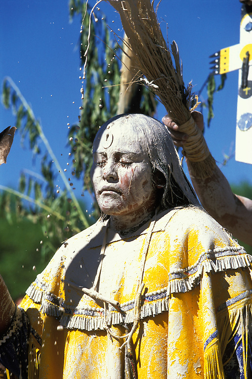 An Apache girl is painted white with sacred clay and corn meal during her Sunrise Dance, a first menstruation rite, on the San Carlos Apache Indian Reservation in Arizona, USA. The painting of the girl is both a blessing and an enactment of certain parts of the Apache creation myth. During the rites the girl becomes Changing Woman, a mythical female figure, and comes into possession of her healing powers. The rites are supposed to prepare the girl for adulthood and to give her a long and healthy life without material wants.