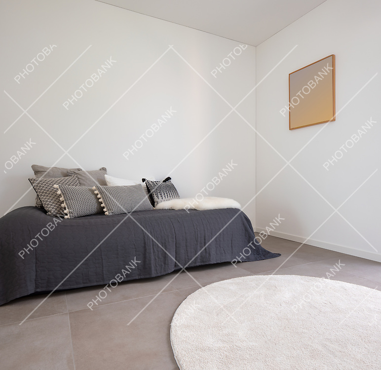 Nice bedroom with a bed and lots of pillows. Detail of the bed with a large white wall, perfect for copy space. Very romantic room. Concept