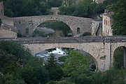 The early school bus crosses one of the bridges at the pretty French medieval walled village of Lagrasse on the River Orbieu, on 23rd May, 2017, in Lagrasse, Languedoc-Rousillon, south of France. Lagrasse is listed as one of Frances most beautiful villages and lies on the famous Route 20 wine route in the Basses-Corbieres region dating to the 13th century.
