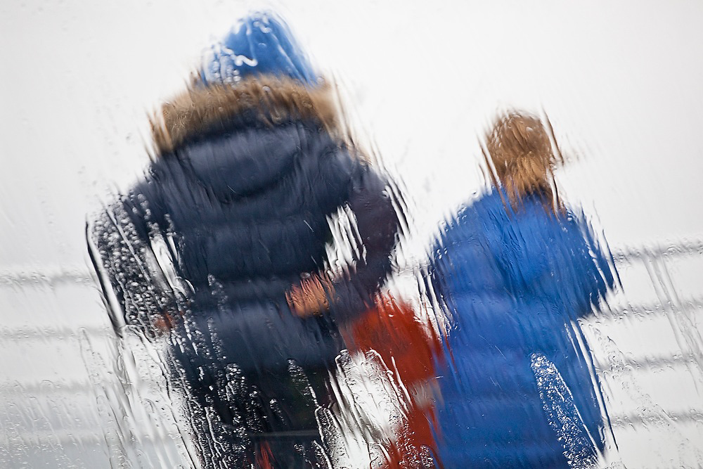 Two girls stand in the rain on the deck of a Stan Stephens cruise boat in Prince WIlliam Sound near Valdez, Alaska.