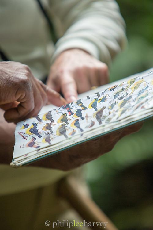 Tourists with bird guide book, Mashpi Lodge, Cloud Forest, Mashpi Reserve, Distrito Metropolitano de Quito, Ecuador