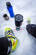 Backcountry skier fixing a hot drink, John Muir Wilderness, Sierra Nevada Mountains, California  USA