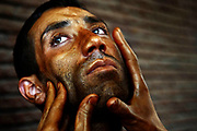 Mohammad Azim, 29, a strong contender for Mr. Kabul in his weight, receives a tanning lotion from his trainer before the semi-finals of the Mr. Kabul competition at the Olympic Stadium, Kabul, Afghanistan, Monday, July 4, 2007.