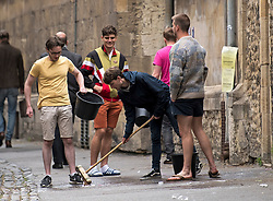 © Licensed to London News Pictures. 04/06/2021. Oxford, UK. Students at Oxford University clean up mess left on a street after other students celebrate finishing their final exams with the tradition known as 'trashing'. Oxford University is attempting to clamp down on the tradition which sees students throwing food, confetti and drink over their classmates. Photo credit: Ben Cawthra/LNP