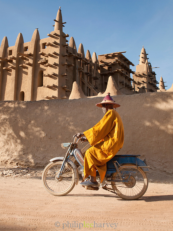 A man in traditional dress rides his moped past the Great Mosque of Djenné, the worlds largest mud built structure and UNESCO heritage site, at Djenné, Mali
