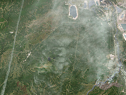 A destructive wildfire burned through Canada's Northern Alberta region, razing neighborhoods in Fort McMurray and displacing tens of thousands of residents.<br /> At 12:34 p.m. local time on May 3, 2016, the Operational Land Imager (OLI) on the Landsat 8 satellite acquired this false-color image of the fire. The image combines shortwave infrared, near infrared, and green light (OLI bands 7-5-3). Near- and short-wave infrared help penetrate clouds and smoke to reveal the hot spots associated with active fires, which appear red. Smoke appears white and burned areas appear brown.<br /> When this image was acquired, the fire was burning southwest of downtown Fort McMurray. Across the day, a growing number of neighborhoods were placed under mandatory evacuation orders. By the evening of May 3, the mandatory evacuation covered all of Fort McMurray - the largest evacuation on record in Canada.<br /> As of May 4, the fire had burned almost 77 square kilometers (7,700 hectares), and its cause was still under investigation. Fire restrictions were in place for most of the province due to hot, dry conditions.<br /> References<br /> Alberta Agriculture and Forestry (2016, May 4) Fort McMurray Area Update. Accessed May 4, 2016.<br /> Alberta Government (2016, May 4) Emergency updates. Accessed May 4, 2016.<br /> Regional Municipality of Wood Buffalo (2016, May 4) Fort McMurray Wildfire Updates. Accessed May 4, 2016.<br /> The Washington Post (2016, May 4) A Canadian oil-sands town is on fire; 80,000 residents must evacuate. Accessed May 4, 2016.<br /> NASA Earth Observatory image by Joshua Stevens, using Landsat data from the U.S. Geological Survey. Caption by Kathryn Hansen.<br />   Please note: Fees charged by the agency are for the agency's services only, and do not, nor are they intended to, convey to the user any ownership of Copyright or License in the material. The agency does not claim any ownership including but not limited to Copyright or License in the attached materia
