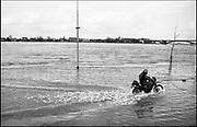 Nederland, Nijmegen 15-1-1988Tijdens de hoge waterstand van de Waal wordt de benedenstad van de Waalkade afgesloten door een barricade van planken met daartussen paardenmest, een zgn coupure. Een man rijdt op een motor door het water. Hoogwater, milieu, klimaatverandering,overstromen,overstromingschade. Wateroverlast. 1988Foto: Flip Franssen/Hollandse Hoogte