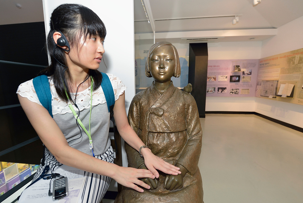 """Yue Takada from Japan holds hands with the statue of a teenage girl who symbolizes """"comfort women"""" in the War & Women's Human Rights Museum in Seoul, South Korea. Created in 2011 for the 1000th weekly vigil demanding action from the Japanese embassy in Seoul, the statue, known as Pyeonghwabi, has a bird perched on its shoulder, signifying peace and freedom. A similar statue sits permanently at the demonstration site, within constant sight of Japanese diplomats.<br /> <br /> Thousands of women, mostly from Korea, were forced into sexual slavery by the Japanese military during World War II.<br /> <br /> Takada visited the museum as part of a seminar on peacemaking for young women from Japan and Korea. The seminary was sponsored by United Methodist Women, the Wesley Foundation in Japan, the Scranton Women's Leadership Center, and the Methodist Theological University."""