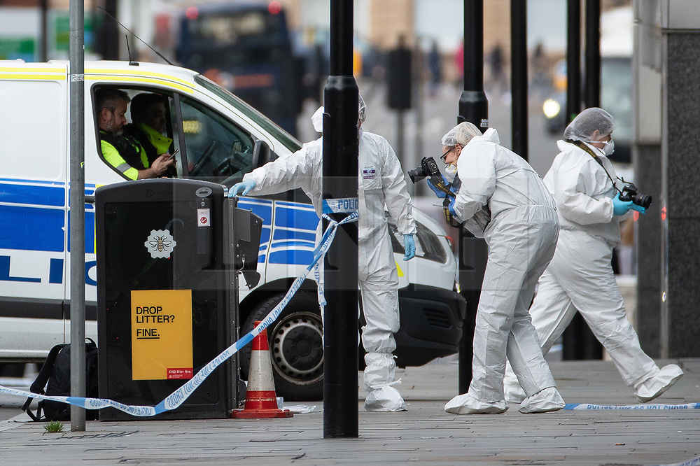 © Licensed to London News Pictures. 11/10/2019. Manchester, UK. Forensic scenes of crime examiners photograph a bin on Exchange Square at the foot of the steps to the Arndale Centre . Terrorism Police are investigating after four people were stabbed during a single attack at the Arndale Centre in Manchester City Centre . Photo credit: Joel Goodman/LNP