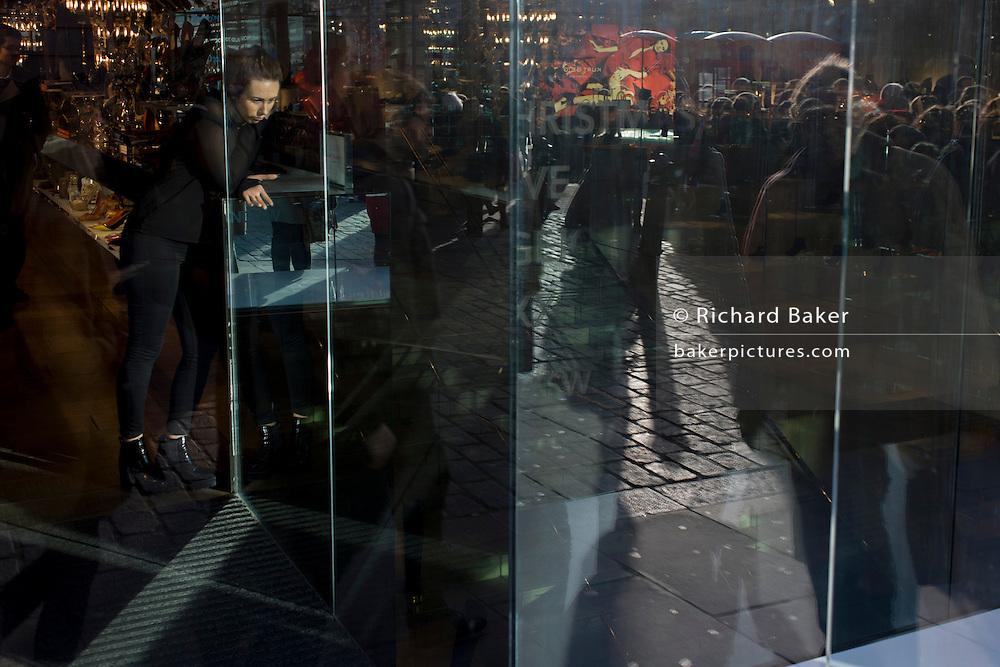 Christmas shoppers seen through the sunlit window of a central London Covent Garden retailer.