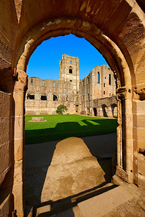 Entrance to central courtyard of Fountains Abbey , founded in 1132, is one of the largest and best preserved ruined Cistercian monasteries in England. The ruined monastery is a focal point of England's most important 18th century Water, the Studley Royal Water Garden which is a UNESCO World Heritage Site. Near Ripon, North Yorkshire, England .<br /> <br /> Visit our MEDIEVAL PHOTO COLLECTIONS for more   photos  to download or buy as prints https://funkystock.photoshelter.com/gallery-collection/Medieval-Middle-Ages-Historic-Places-Arcaeological-Sites-Pictures-Images-of/C0000B5ZA54_WD0s