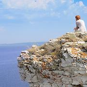 "Girl sitting on a rock of Devia hill and observing Volga reservoir in Russian National Park ""Samarskaya Luka"""