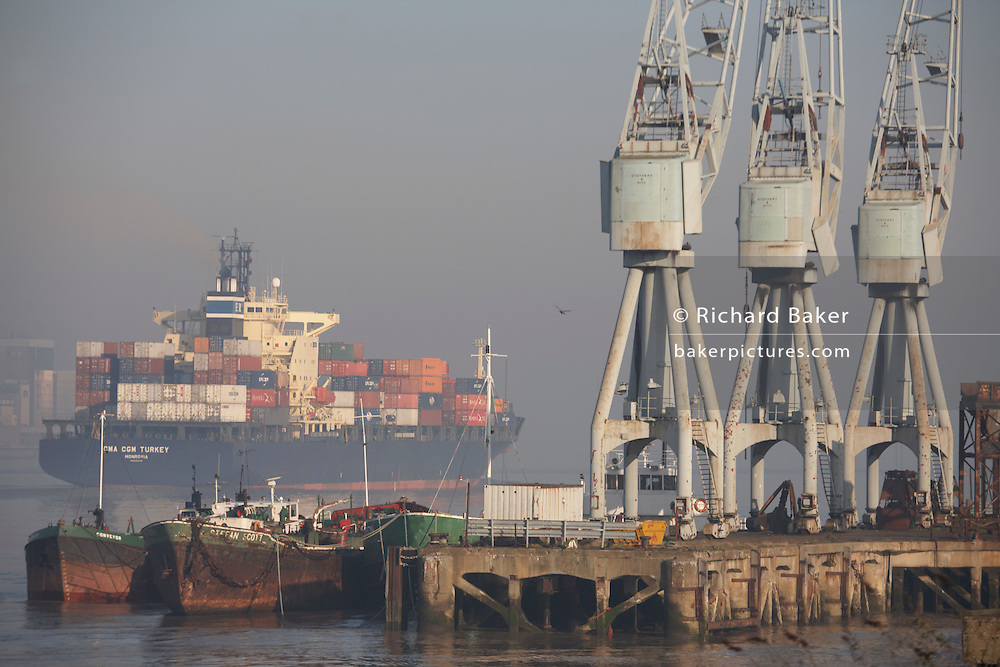 Giant cargo container ship on the River Thames eases downstream past old dock cranes at Gravesend, towards open sea at Southend