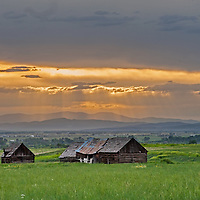 The sun's rays poke between clouds over old farm buildings in the Gallatin Valley near Bozeman and Belgrade, Montana.