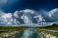 Billowing storm clouds provide a dramatic backdrop to the landscape around the canal along Coconut Palm Drive (SW 248th Street) near Homestead, Florida. WATERMARKS WILL NOT APPEAR ON PRINTS OR LICENSED IMAGES.