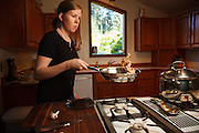 USA, Oregon, Eugene, young woman sauteeing walnuts for salad. MR