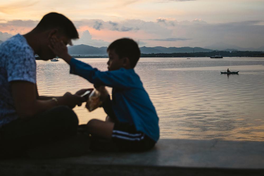 Puerto Princesa, Palawan, Philippines - July 5, 2019: A father and son sit at sunset at the Puerto Princesa City Baywalk Park.
