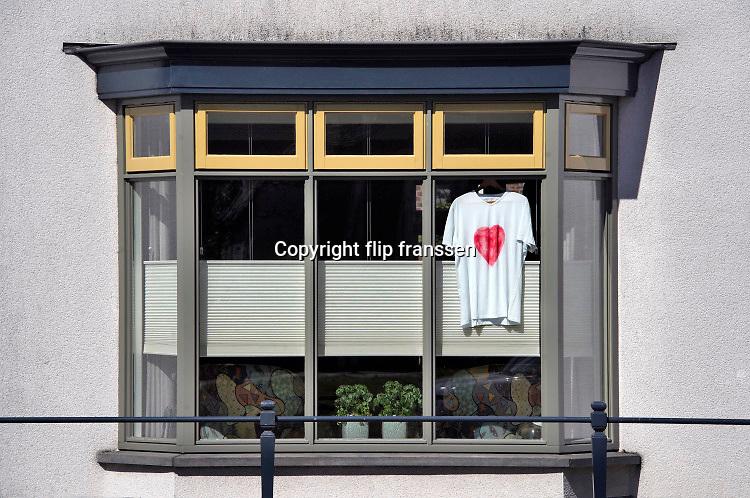 Nederland, Wijchen, 5-4-2020  Achter het raam van een woning is een shirt opgehangen met daarop een groot rood hart als dank en respectbetuiging aan het personeel in de zorg en op de ic die met het coronavirus te maken hebben .  Foto: Flip Franssen