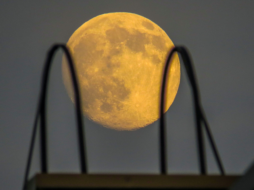The red moon shines over the building's ladder.