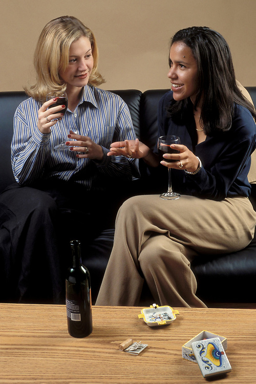Young Anglo woman and African-American woman sit on couch after work and relax with some wine and a cigarrette.  Model Release.<br /> ©Bob Daemmrich