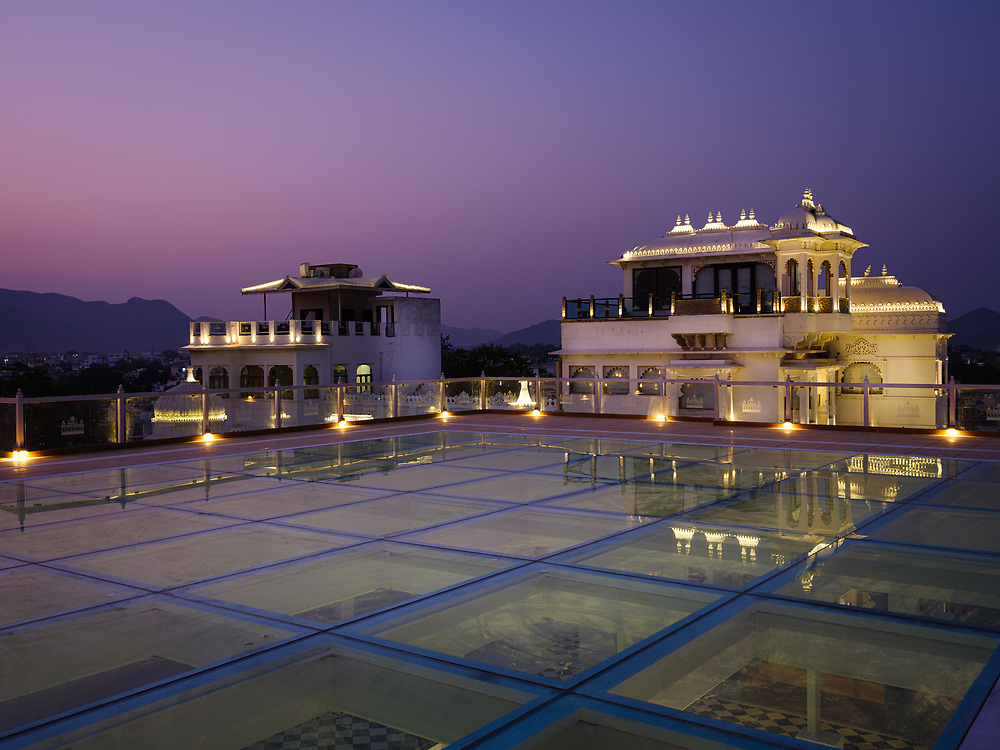 """UDAIPUR, INDIA - CIRCA NOVEMBER 2018:  Rooftop of the Hotel Udai Kothi in at night in Udaipur. The city is the historic capital of the kingdom of Mewar. Surrounded by Aravali Range, which separates it from Thar Desert, and full of lakes Udapiur is also known as the """"City of Lakes"""" and dubbed as the most romantic spot of the Indian Continent."""
