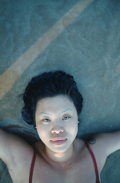Oriental female lying down on beach/water looking directly up at the camera